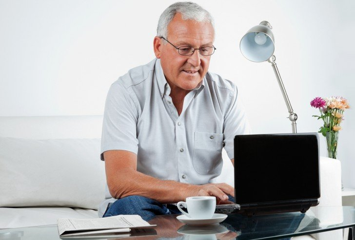 Senior man working on laptop at home